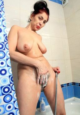 Mature woman washes her hairy bush in..